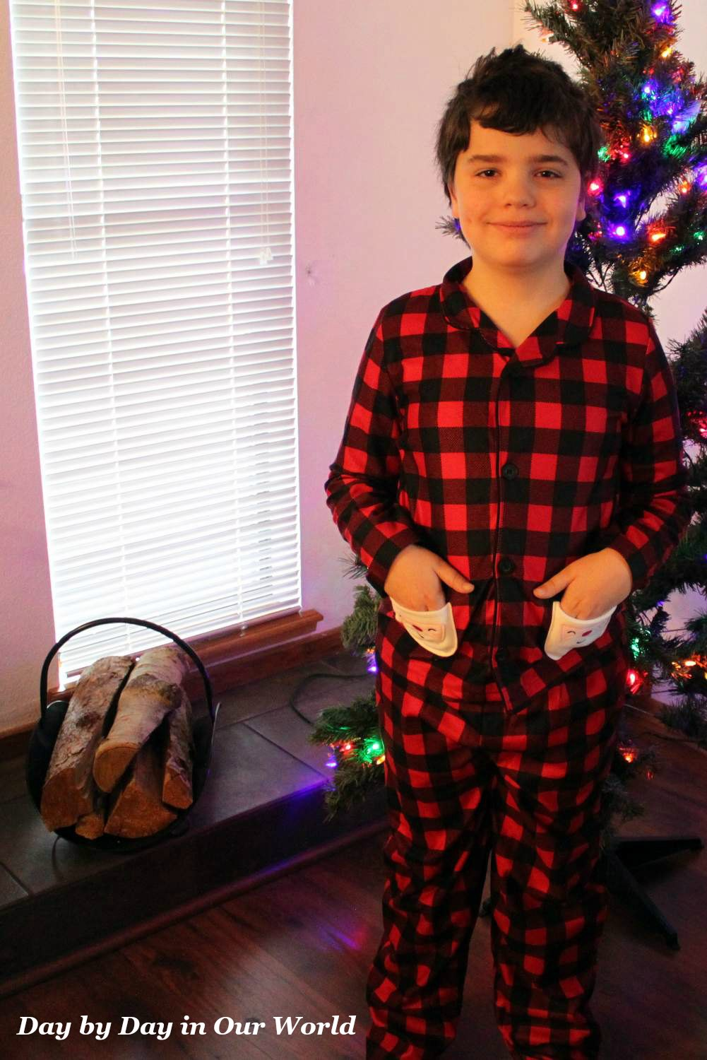 Ready to decorate the tree in his warm flannel Santa pajamas from Carters.