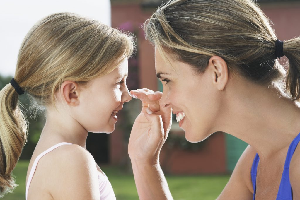 Mother Applies Sunscreen to daughter's nose to avoid sun damage on face
