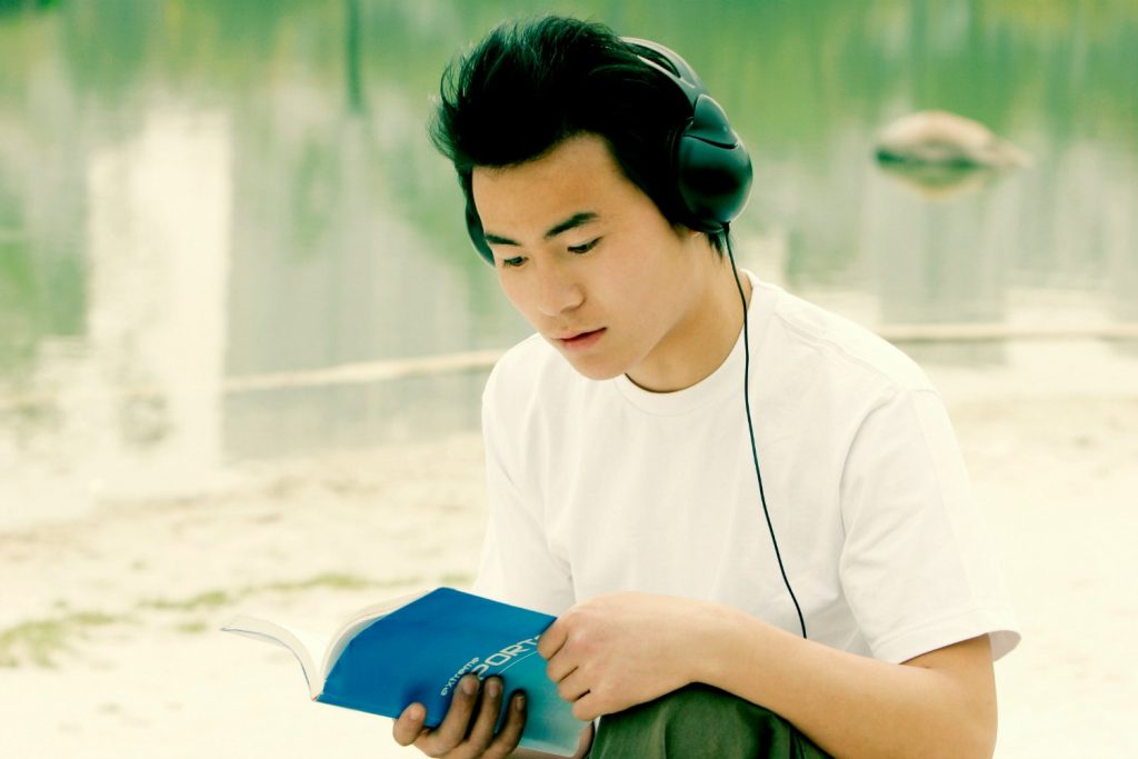 Man Listening to Audio while looking at book